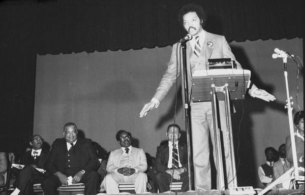 Men watching Civil rights leader Jesse Jackson delivering a speech in an auditorium - Tallahassee, Florida.