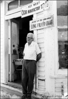 Rex Shaw standing in front of his factory on Fleming Street: Key West, Florida (197-)