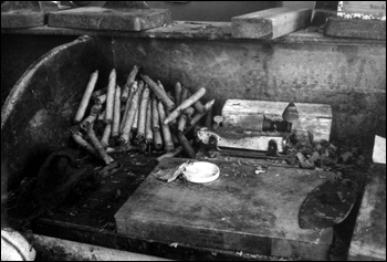 "Cigars and materials used in creating them on a work station desk top inside ""Rex of Key West"" cigar factory (between 1970 and 1985)"