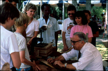People watching Raphael Ozambela roll cigars at the 1986 Florida Folk Festival: White Springs, Florida (1986)