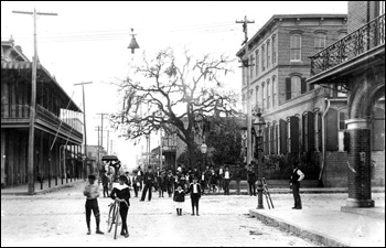People stand on the intersection of 14th Street and 9th Avenue in Ybor City: Tampa, Florida (19--)