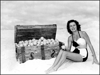Margie Fletcher in a beach scene, posing with an orange-filled treasure chest: Winter Haven, Florida (1949)