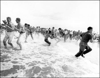"Segregationists trying to prevent blacks from swimming at a ""White only"" beach (June 25, 1964)"