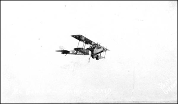 Stuntman hanging from wing of flying Jenny: Daytona Beach, Florida (1923)
