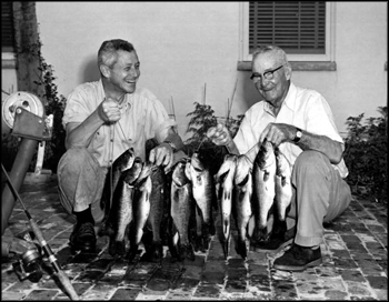 Governor LeRoy Collins helps his father, Marvin Sr., hold up their catch of black bass (1958)