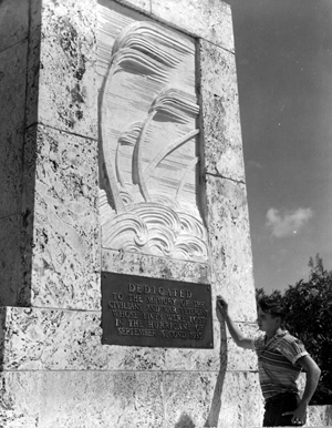A young man reading the bronze plaque on the memorial for the 1935 hurricane victims: Islamorada, Florida