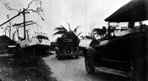 Cars driving by boats washed ashore from the 1926 hurricane: Miami, Florida