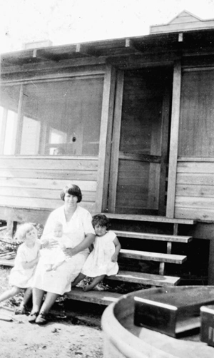 Woman and children on the steps of their new home