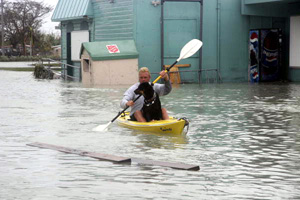 Man kayaking with dog on Flagler Avenue by the Salvation Army store: Key West, Florida (2005)