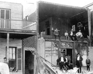 Group of people gathered around building devastated by storm: Cedar Key, Florida (1896)