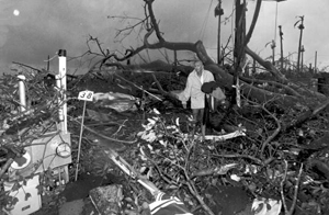 Harold Wilkins walks through rubble left by Hurricane Andrew: Florida City, Florida (1992)