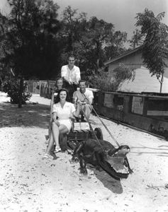 Two men and two women posing with a concrete alligator (1950s)