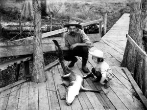 Leigh M. Pearsall and daughter Edna with alligator on dock: Melrose, Florida (ca. 1905)