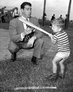 Joe DiMaggio showing three year old Larry Valencourt how to hold a bat: West Palm Beach, Florida (1948)