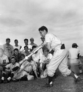 "Phil Rizzuto, N.Y. Yankees bunting wonder, illustrates his unusual bunting ""twist"" before boys on bench: Bartow, Florida (1948)"
