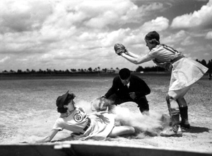 All American Girls Professional Baseball League player Marg Callaghan sliding into home plate as umpire Norris Ward watches: Opa-locka, Florida (1948)