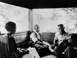 Gabriel Brown playing guitar as Rochelle French and Zora Neale Hurston listen: Eatonville, Florida