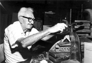 Rex Shaw turning press on cigars at his store on Fleming Street: Key West, Florida (197-)