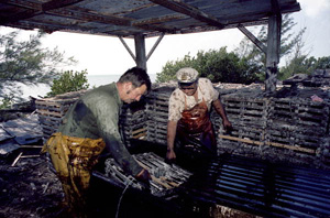 Captain Roche and mate Clyde Carey dipping a crawfish trap in creosote to protect it from rot: Stock Island, Florida (1974)