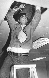 Florida Senator Bob Graham pushing speaker wire into a drop ceiling (1977)