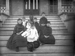 Children and their baby sitter on the steps of the Leon Hotel