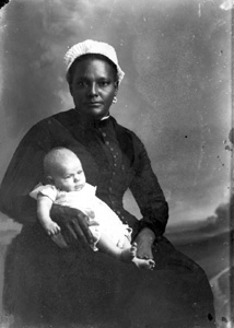 White-capped nurse holding an infant