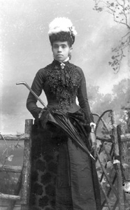 Woman wearing beaded dress, with hat
