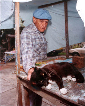 Mario Sanchez taking a break from his art work to pet his cat: Key West, Florida (1992)