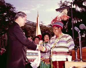 Title: Seminole Tribe of Florida Chairman Billy Osceola presenting Governor Haydon Burns with patchwork jacket at Burn's gubernatorial inauguration: Tallahassee, Florida (1965)
