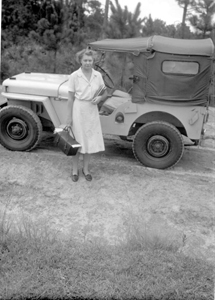 Public health nurse standing beside her jeep (ca. 1948)