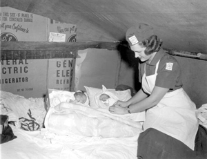 Florida State University public health nurse checking twins born to migrant worker family (195-)