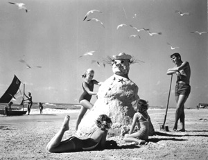 Three girls making a &quot;sandman&quot; at the beach (1964)