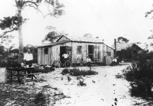 Japanese American men sitting by a home: Yamato, Florida (19--)