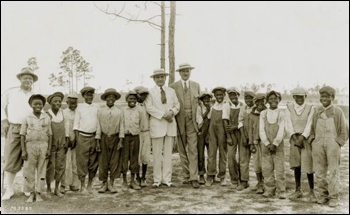Golf Pro Alec Smith (left) and others posing with caddies: Miami, Florida (1920s)