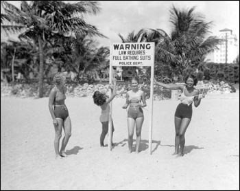 Young women making fun of sign at beach requiring full bathing suits: Miami, Florida (1934)