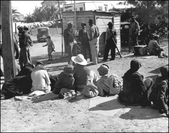 Migrant workers waiting for a truck to take them to the bean fields: Lake Harbor, Florida (1939)