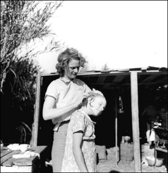 Migrant worker cleaning her daughter's scalp: Belle Glade, Florida (1939)