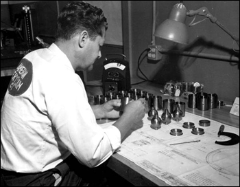 A worker inspecting finished beryllium parts at the Visioneering Company: Sarasota, Florida (1959)