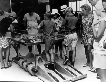 Boys look at an exhibit while standing on the tread of a crawler-transporter: Cape Canaveral Florida(19--)