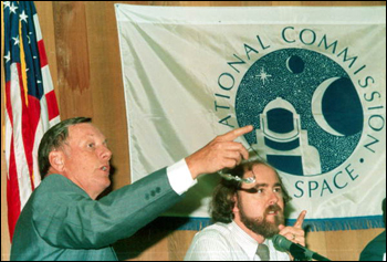 Neil Armstrong and Leonard David gesture during a meeting of the National Commission of Space: Tallahassee, Florida (1985)
