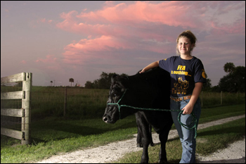 Kaley Dees with cow. Okeechobee, September 2008.