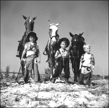 Three boys dressed as a cowboys with their horses: Saint Petersburg, Florida (1947)