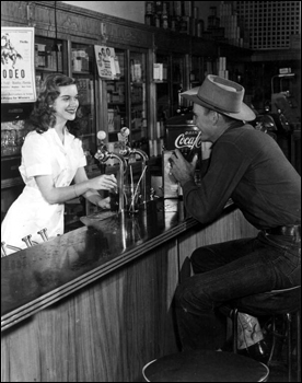 Unidentified cowboy gets a soda from the soda shop: Bonifay, Florida (1949)