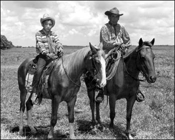 Seminole Indian cowboy Charley Micco and grandson Fred Smith on horseback in a cattle ranch: Brighton Reservation, Florida. (1950)