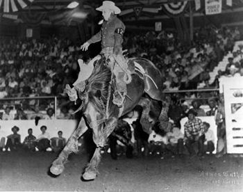 Vick Blackstone riding bronco at rodeo