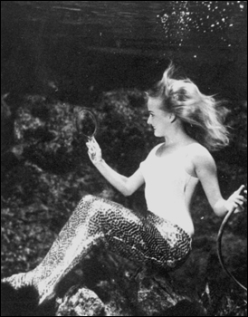 Mermaid at Weeki Wachee Springs viewing herself in a mirror (1969)