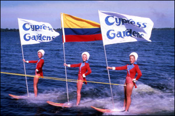 View showing water skiers holding flags during performance at the Cypress Gardens theme park in Winter Haven, Florida (19--)