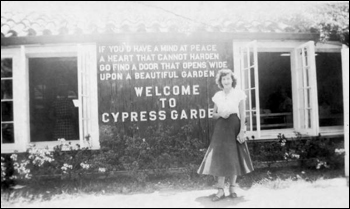 Unidentified lady stands in front of the sign for Cypress Gardens: Winter Haven, Florida (19--)