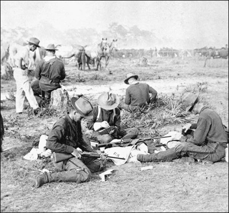 Rough Riders filling belts with cartridges (1898)