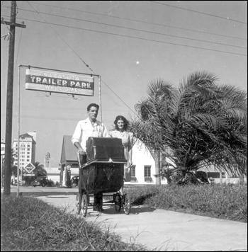Al and Roey Stickles pushing a baby stroller through a trailer park in Sarasota, Florida (1946)